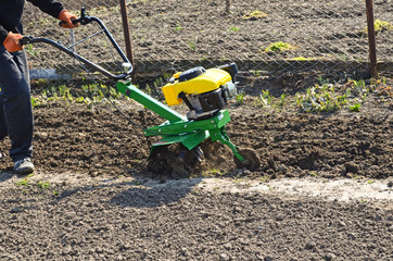 The farmer processes a spring field the motor-block