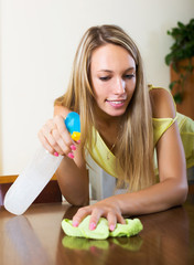 Young smiling housewife dusting table
