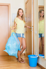 Housewife with bags of garbage indoor