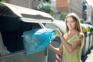 Woman with trash bags near garbage bin