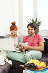 Couple at the Couch with Laptop, Card and Money