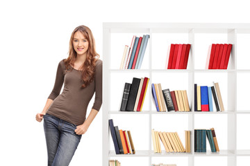 Casual young woman leaning on a bookshelf and