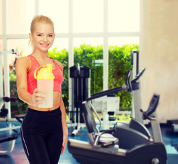 smiling sporty woman with protein shake bottle