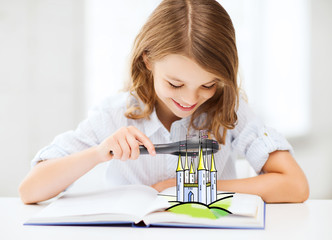 girl with book looking to castle through magnifier