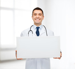 smiling male doctor holding white blank board