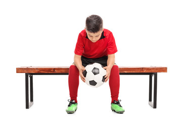 Worried boy in football shirt sitting on a bench