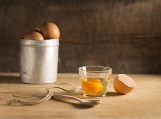 uovo crudo in bicchiere su tavola legno