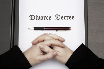 Woman with clasped hands on divorce decree