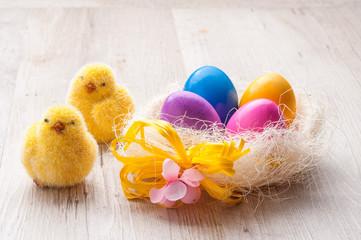 Nido con uova pasquali colorate e pulcini sul tavolo