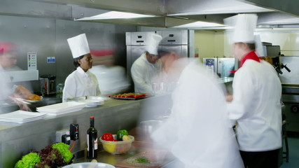 Time lapse of busy team of chefs preparing food in a commercial kitchen