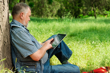 old man sitting under a tree with the tablet
