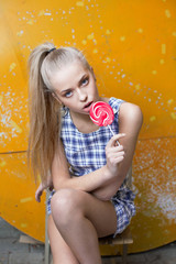 Young blonde girl with a lollipop