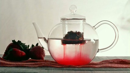 teapot with strawberry infusion tea and tea cup