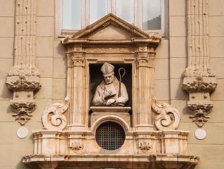 Sculpture of Catholic priest is decorated old building