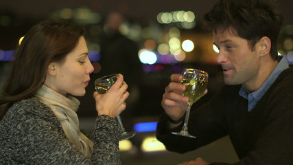 Couple drinking wine raise their glasses for a toast