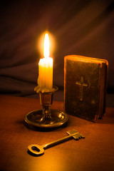 Old bible and candle with key on a wooden table