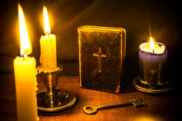 Bible and three candles with key on a wooden table
