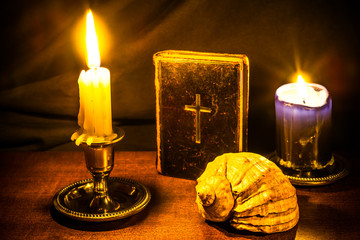 Bible and two candles with sea shell on a wooden table