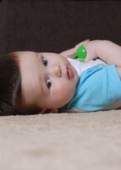 Baby boy lying on the floor looking to camera