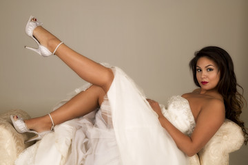 woman in a wedding dress laying back with one leg up smiling