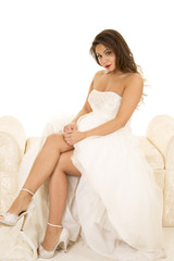 woman in a wedding dress sitting legs showing serious