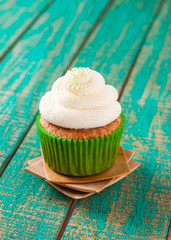 cupcakes with cream on a green background