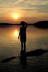 kobieta w jeziorze o zachodzie słońca