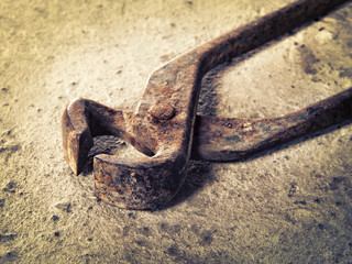 old iron pincers on concrete closeup