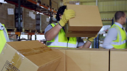 Warehouse workers in high visibility clothing taking brown boxes from a pallet