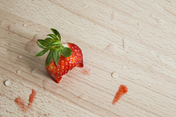 Eaten isolated strawberry head on a wooden background