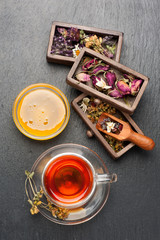Herbal tea with honey, dried herbs and flowers. top view