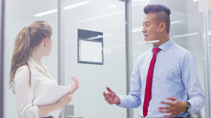 Businessman and woman in discussion in modern city office. In slow motion.