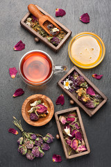 Herbal tea with honey, dried herbs and flowers on black stone