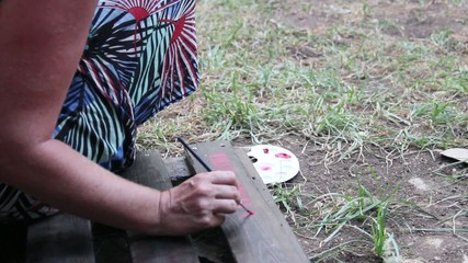 womans hand painting letters on wood