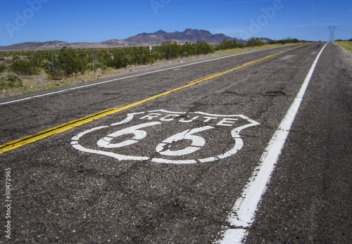 long road with a Route 66 sign painted on it Poster