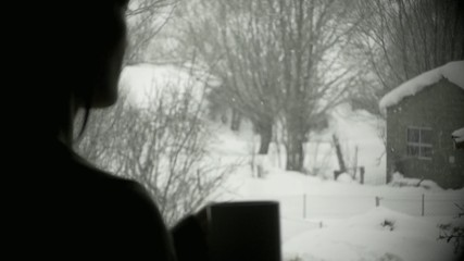 Girl at window while snowing
