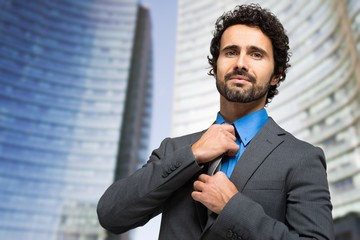 Portrait of a confident businessman adjusting his tie