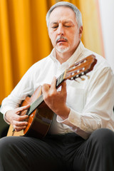 Mature man playing a classical guitar