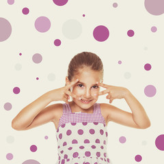 Happy playful little girl in dress with purple dots