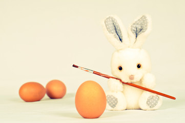 Toy rabbit with eggs and painting brush