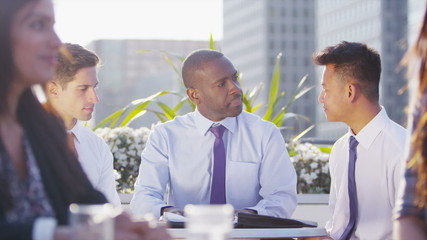 Mixed ethnicity business team in open air city meeting shake hands on a deal
