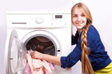 Beautiful girl puts laundry in the washing machine