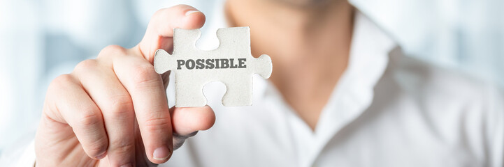 Businessman holding puzzle piece with Possible text
