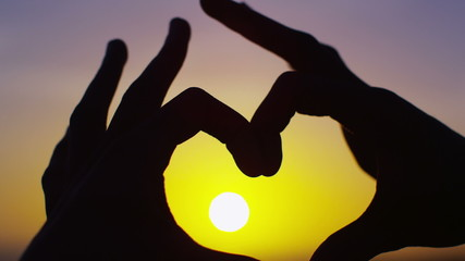 Hands join together to make a heart shape, outdoors on a beach at sunset