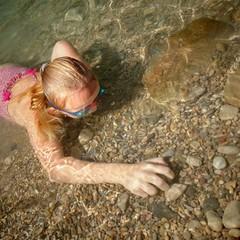 Niña buceando en río