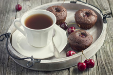 cherry cupcakes and cup of tea on a wooden tray