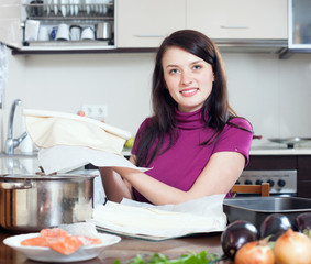 Smiling woman cooking fish pie with  store-bought dough