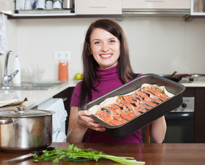 happy woman cooking fish pie with salmon