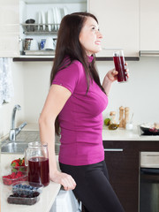 Smiling woman drinking red fruit-drink