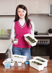 brunette woman with various seedlings